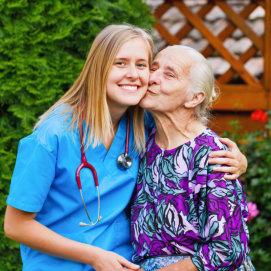 senior woman kissing her caregiver's cheek