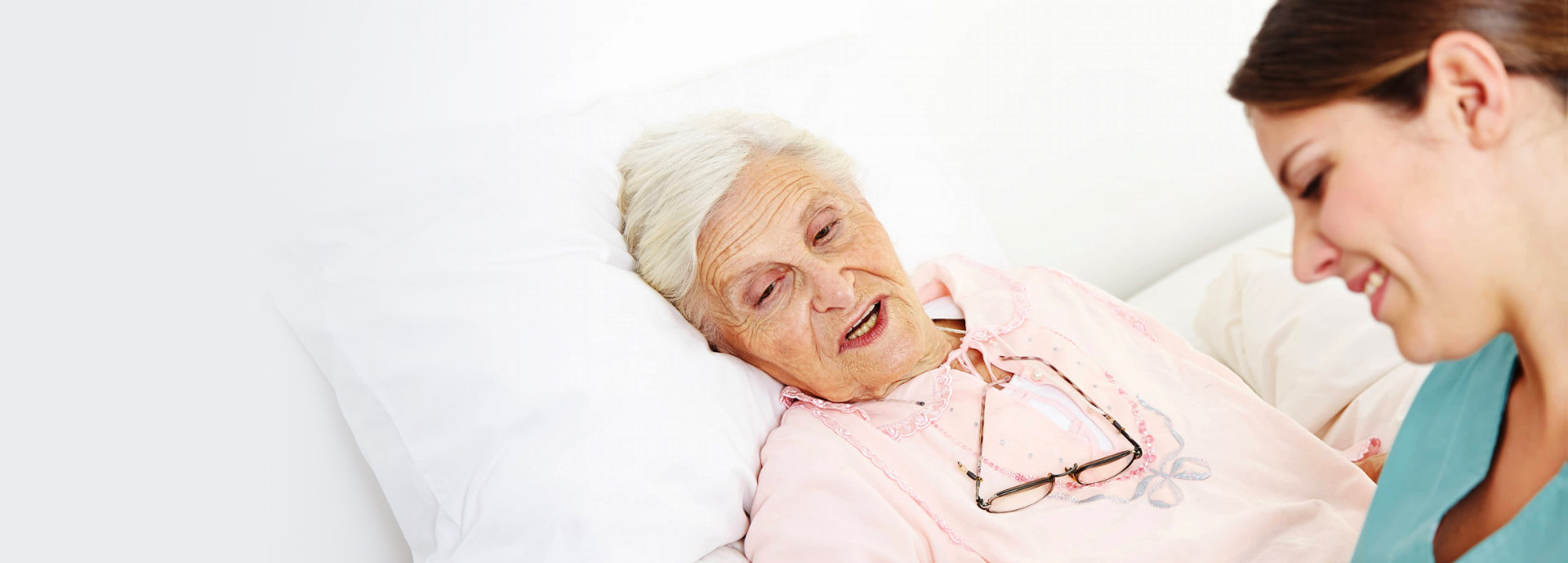 happy senior woman on bed with caregiver beside her