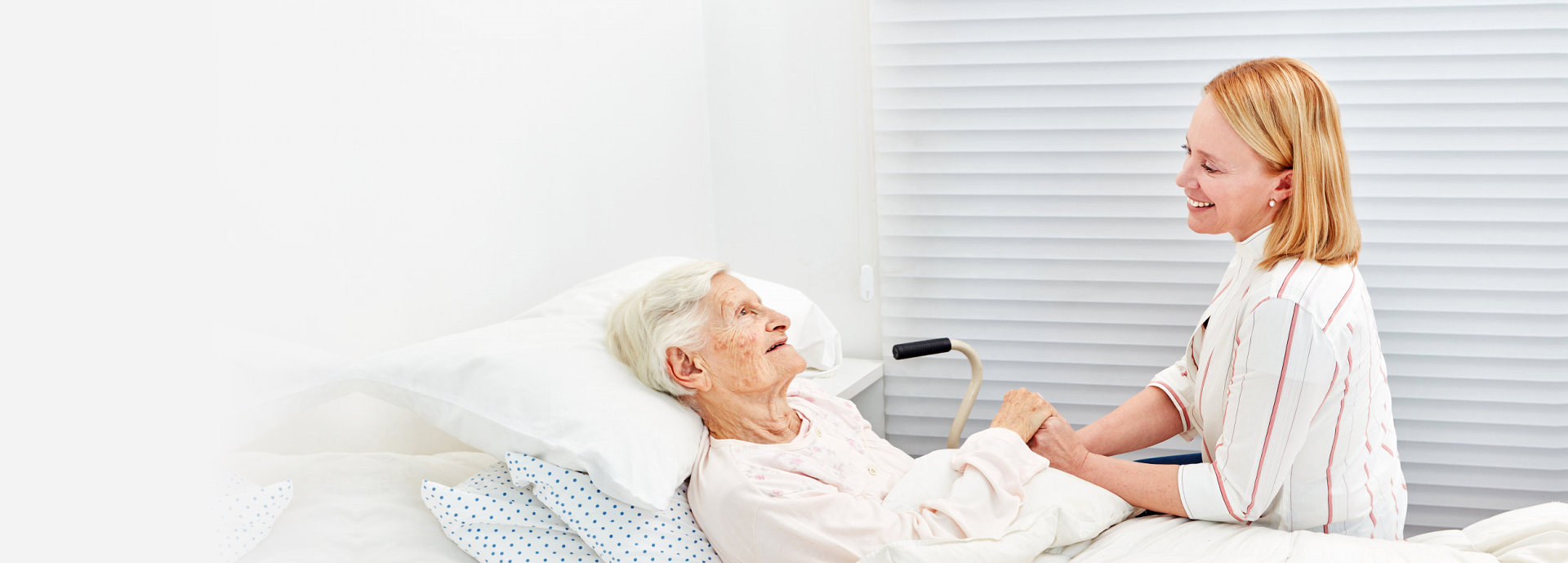 senior woman on bed talking to her caregiver