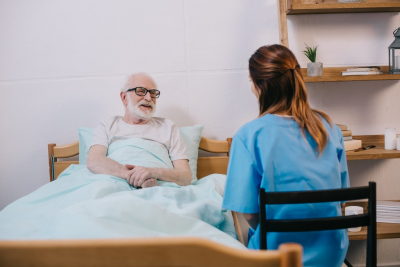 smiling old patient in bed talking to his caregiver