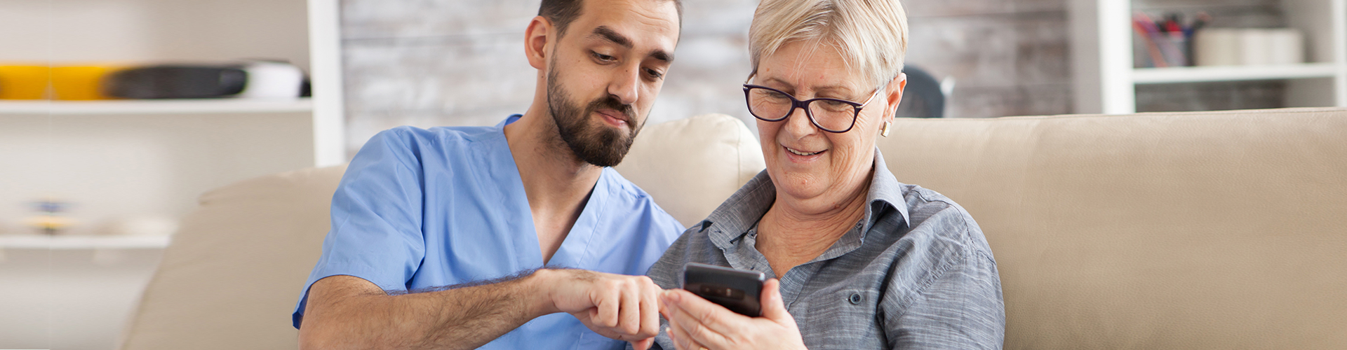 caregiver guiding a senior woman in using her phone